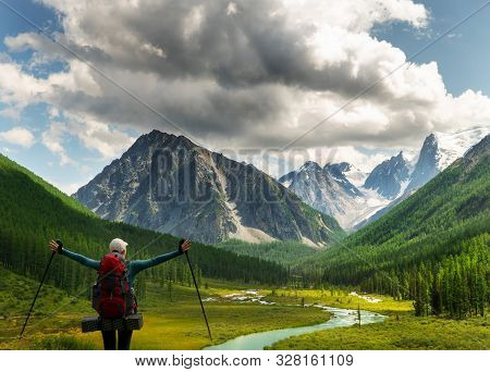 A Girl With Her Hands Up Standing By The Mountain River, Looking At The Beautiful Summer Landscape.