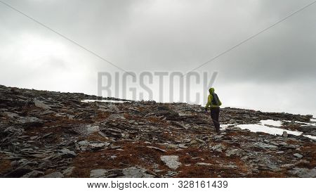 Prepared For Bad Weather Conditions, The Trail Runner Runs Along A Stone Path In The Mountains. Wate