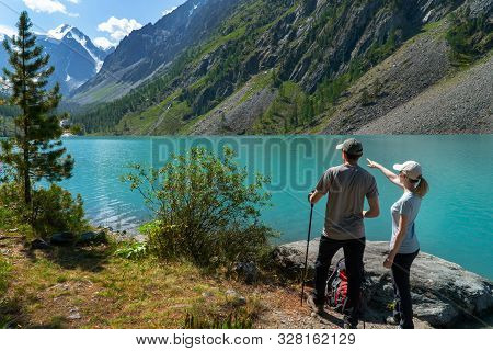 Young Tourists With Backpacks On The Shore Of The Lake With Turquoise Water Enjoy The View Of The Mo