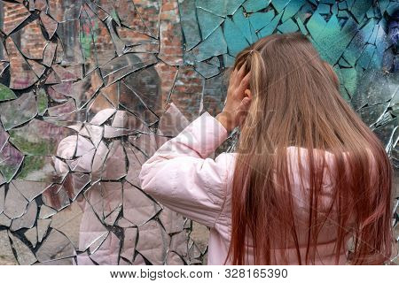 Young Girl Looks In A Broken Mirror And Suffers And Keeps Herself By The Head. Eyes Are Closed. The