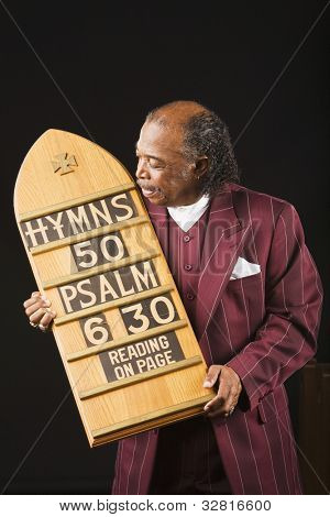 Senior African man holding hymn board