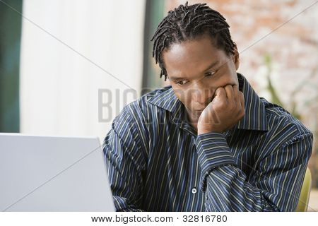 African man looking at laptop