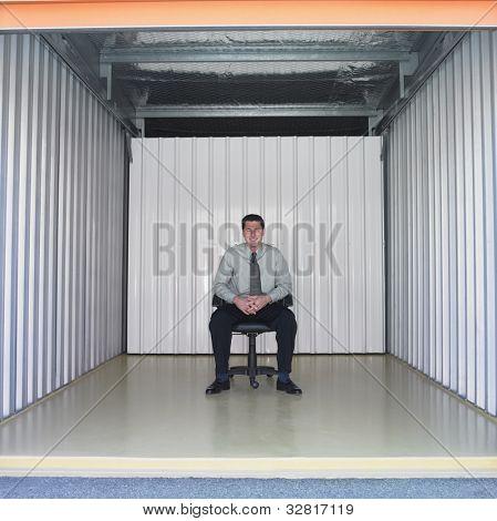 Businessman sitting in empty storage space
