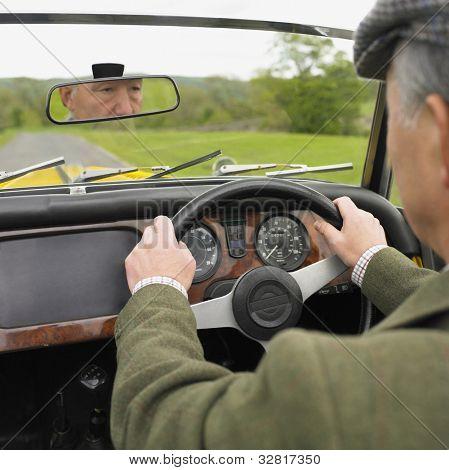 Senior Asian man driving old fashioned car