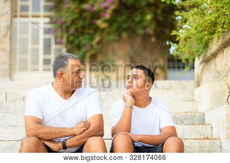 Teenager Son And Senior Father Sitting On Stairs Outdoors At Home, Talking.