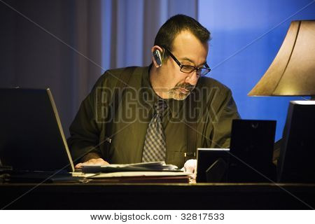 Hispanic businessman wearing hands free device