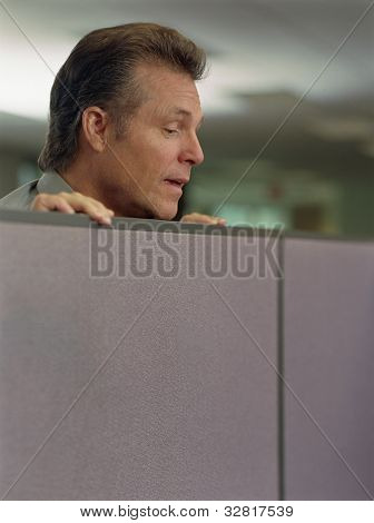 Businessman looking over cubicle wall