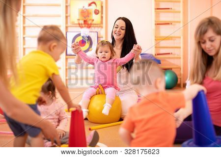 Yoga For Baby. Child-friendly Fitness For Women With Kids. Mothers With Happy Toddlers Doing Exercis
