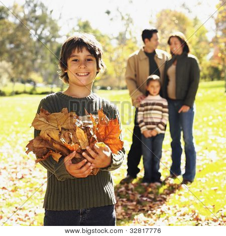 Mixed Race boy playing in autumn leaves