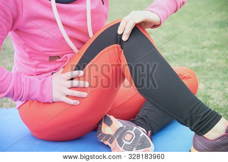 Female Athlete Suffering Form Running Knee Or Kneecap Injury During Outdoor Workout On Dirt Road.
