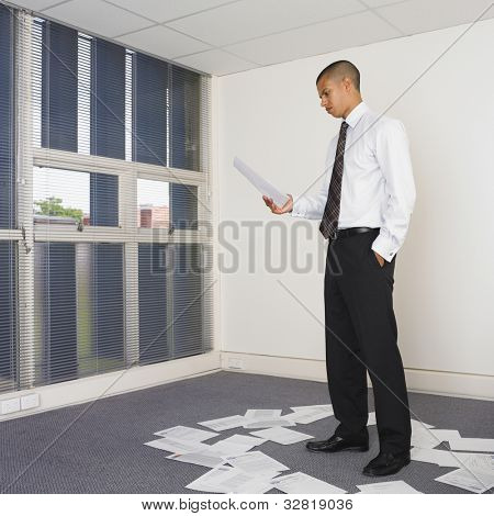 Mixed Race businessman sorting paperwork
