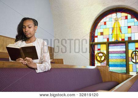 African American woman reading Bible in church