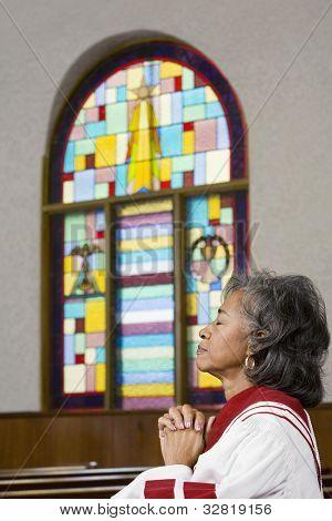 African American female Reverend praying