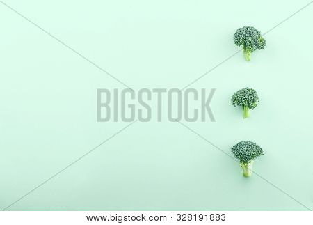 Brocolli . Layout  Made  Of Three Green Cabbage Florets Over Green Background. Minimalism.flat Lay.