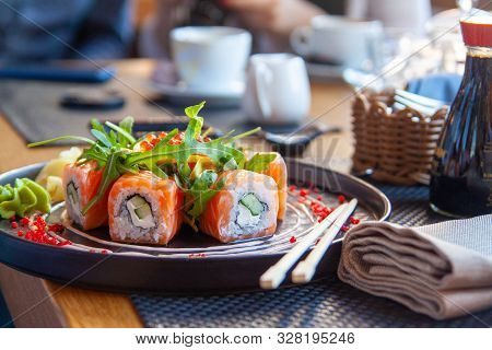 Sushi Roll Japanese Food In Restaurant. California Sushi Roll Set With Salmon, Vegetables, Flying Fi