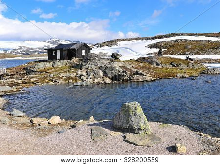 Snowy Nordic Landscape With Black House On Lake