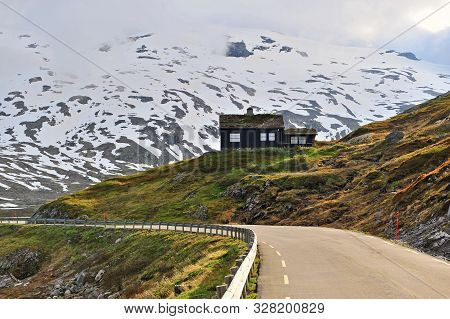 Famous Snow Road In Norway With Black Wooden House Under Mountains