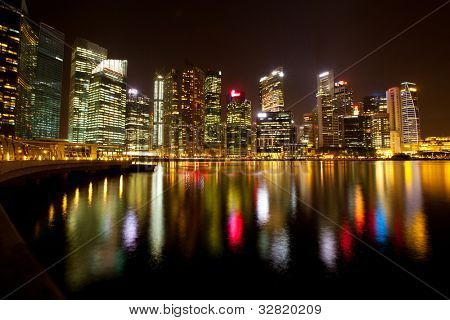 A view of Singapore business district Marina Bay in the night time with water reflections.