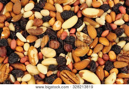 Mixed Shelled Nut Kernels And Raisin Background With Brazil Nuts, Peanuts, Hazelnuts, Almonds, Pecan