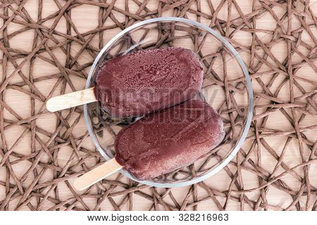 Top View Fresh Raw Popsicles On Sticks Coated With Chocolate Glaze Lay In Glass Transparent Bowl On
