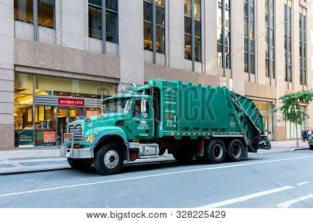 New York, United States - September 20, 2019: A Large Green Trash Truck In The Streets Of Manhattan.