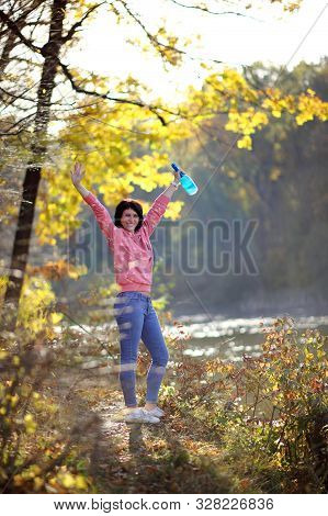 Girl In The Yellow Autumn Forest. Beautiful Mature Woman In A Forest With A Bottle Of Champagne In H