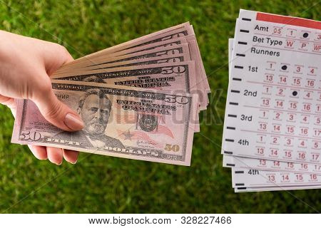 Cropped View Of Woman Holding Dollar Banknotes Near Betting Lists On Green Grass, Sports Betting Con