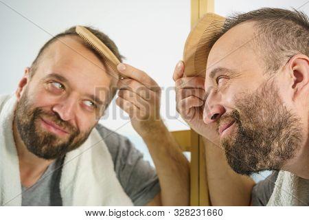 Man Using Comb In Bathroom
