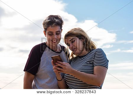 Lesbian Couple Is Having Fun With A Smartphone In A Meadow