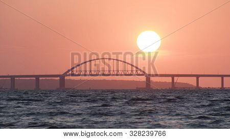 Stunning View Of The Beautiful Sunset Over The Big River And The Bridge, Time Lapse Effect. Shot. Br