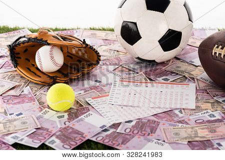 Baseball Glove And Ball, Soccer, Tennis And Rugby Balls Near Betting Lists On Euro And Dollar Bankno