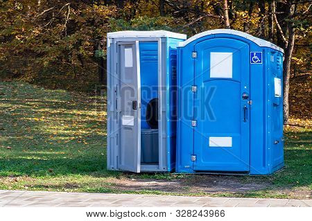 Two Portable Toilets In A Park.one Of Them For Disabled.