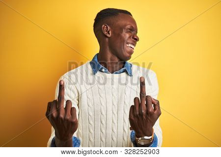 African american man wearing denim shirt and white sweater over isolated yellow background Showing middle finger doing fuck you bad expression, provocation and rude attitude. Screaming excited poster