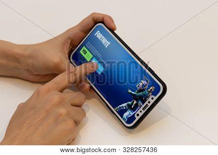 Elva, Estonia November 15, 2018 Girl Holding Iphone With Online Fortnite Game Epic Games, Pressing N
