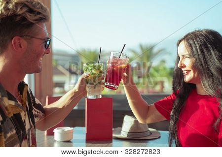 Happy Couple Drinking Cocktails At Party Outdoor. Young Millennials People Having Fun At Weekend Sum