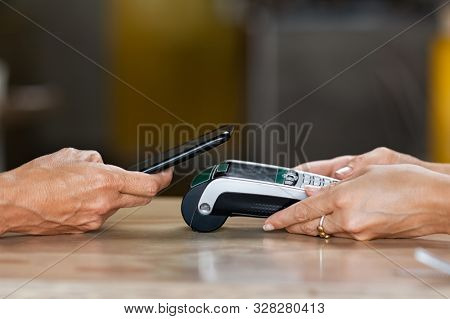 Closeup of woman hand paying a bill through smartphone using NFC technology. Closeup of hand holding pos terminal to receive payment using phone. Customer using mobile to make payment with contactless