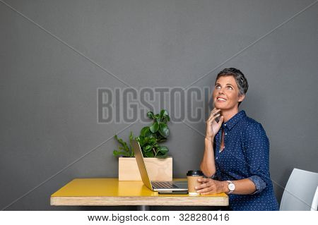 Thoughtful mature businesswoman looking away. Senior woman working on computer and looking up on gray wall while thinking. Pensive business lady isolated against grey background contemplating plans.
