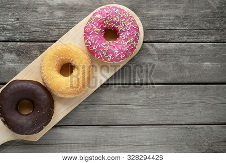 Three Different Donuts, Chocolate Donut, Pink Icing And Without Icing On A Wooden Cutting Board On A