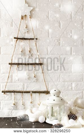 poster of Scandinavian cozy home decor. Wooden stylish Christmas tree in scandinavian style against the background a white brick wall. White lantern, scarf and Christmas garland.