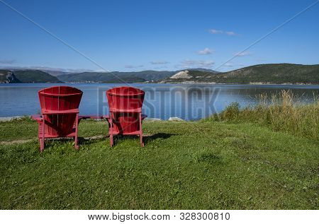 Two Red Adirondack Chairs With A View Of Bonne Bay And Tablelands