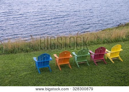 A Row Of Bright And Colorful Adirondack Chairs Facing The Ocean