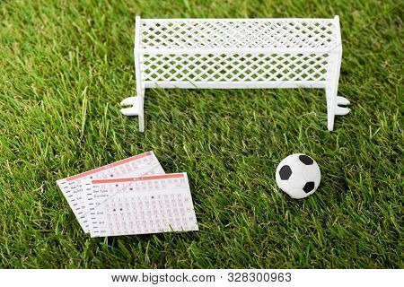 Toy Soccer Ball Near Miniature Football Gates And Betting Lists On Green Grass, Sports Betting Conce