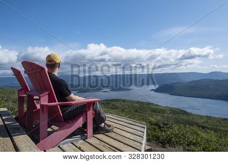 Man Sitting In A Red Adirondack Chair On  Top Of The Lookout Trail In Woody Point, Gros Morne Nation