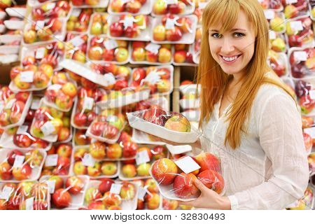 Blonde girl wearing white shirt chooses packed apples in store; shallow depth of field