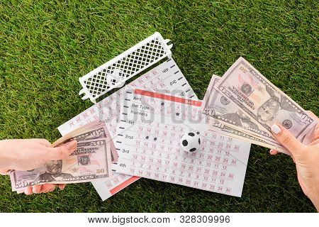 Partial View Of Female Hands With Dollar Banknotes Near Toy Soccer Balls, Gates And Betting Lists On