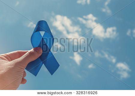 Hand Holding Blue Ribbon On Blue Sky Background , Prostate Cancer Awareness, Men Health Awareness, N