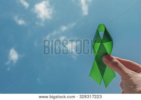 Hand Holding Green Ribbon Over Blue Sky, Mental Health Awareness And Lymphoma Awareness, World Menta