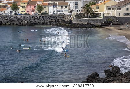 People Surfing And Swimming On A Beach In Sao Roque, Sao Miguel Island, Azores