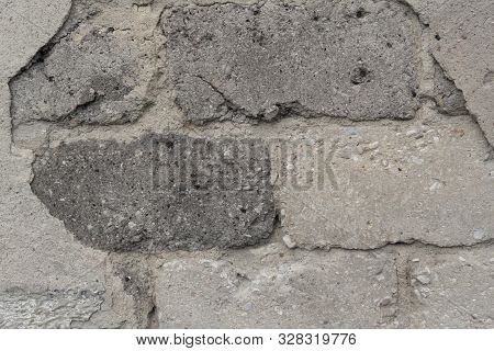 Old Ruined Gray Wall Of Bricks And Cement Plaster. The Concept Of Breaking Down Fundamentals Over Ti
