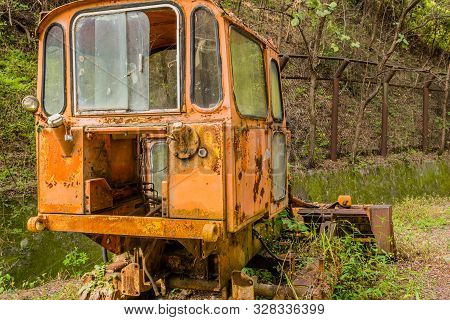 Rear View Of Old, Rusted, Broken Down Bulldozer Sitting On Abandoned Unused Road In Wilderness.